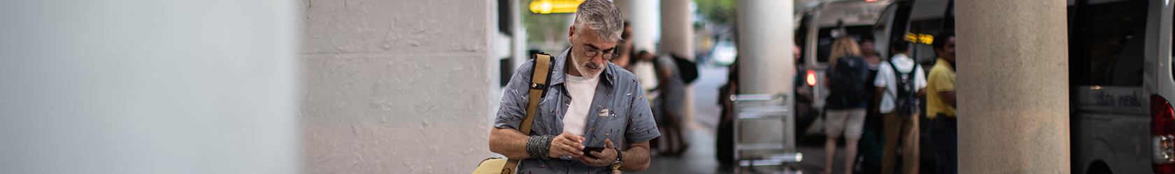 Man is on his mobile phone in an airport, wearing short-sleeved shirt and shorts.