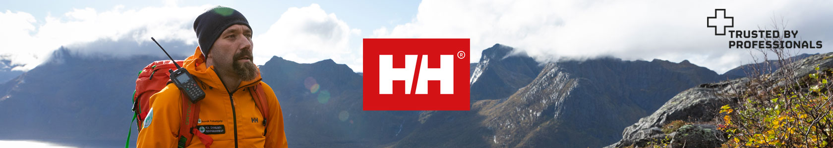 A man wearing a orange Helly Hansen jacket, a scenery of mountains touching the clouds and the Helly Hansen logo in the centre