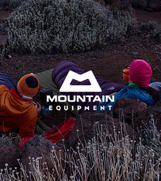 Two people wearing and equipped with the Mountain Equipment sleeping bags and mats resting among rocks