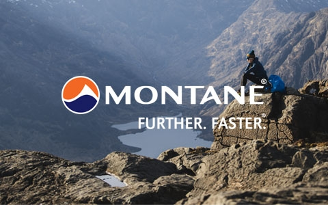 Woman sitting on a rock and looking over a rock valley, wearing Montane gear