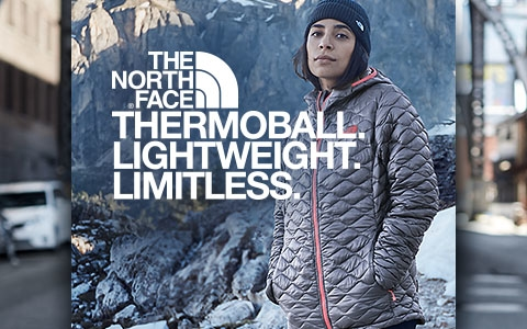 A woman, wearing a The North Face Thermoball jacket, is somewhere in the mountains with snow around and some fur trees.