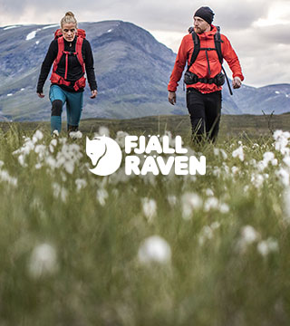 Woman and man walking in the mountains wearing Fjallraven gear.
