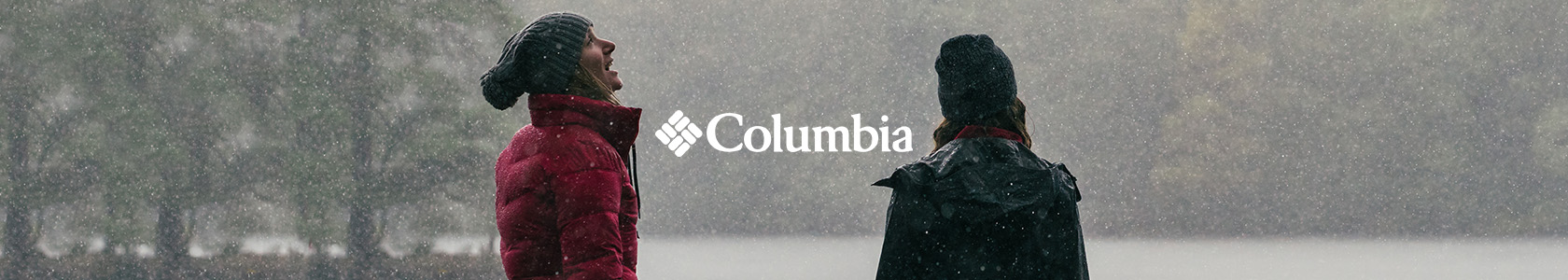 Two people are standing by a lake during falling snow, wearing Columbia clothing.