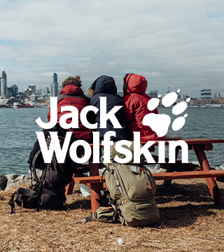 Three people sitting on a bench in Jack Wolfskin gear and enjoying the river view next to a city