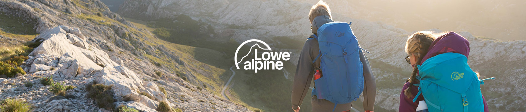 Woman walking through woods in Lowe Alpine gear.