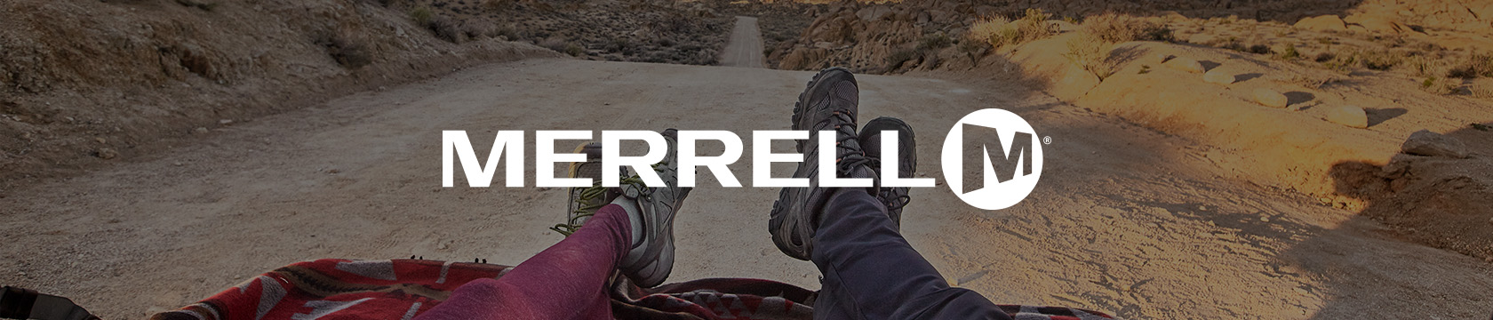 Female and male legs in Merrell footwear in the middle of a sandy road.