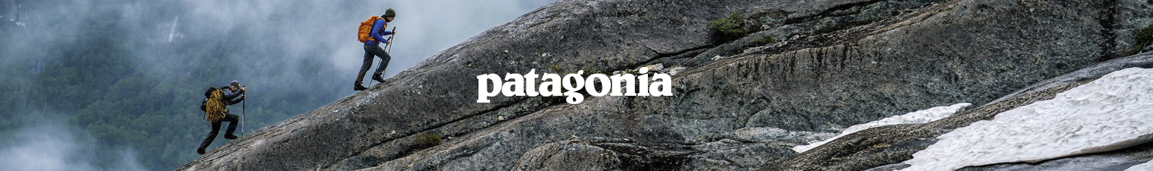 Two people are walking up a rocky mountain, wearing Patagonia gear with walking poles.