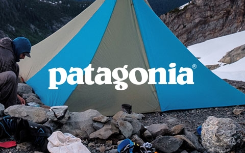 Two people setting up camp on a rocky mountain, wearing Patagonia gear.