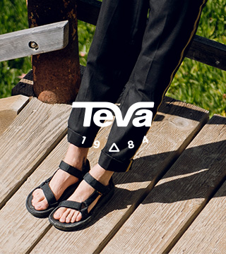 Person's feet standing on wooden stairs wearing Teva sandals.