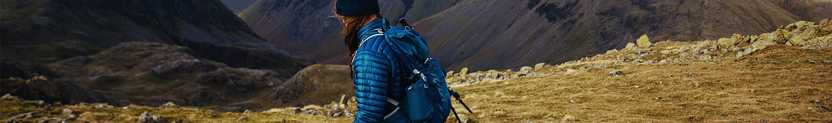 A person is walking on mountains, wearing a rucksack