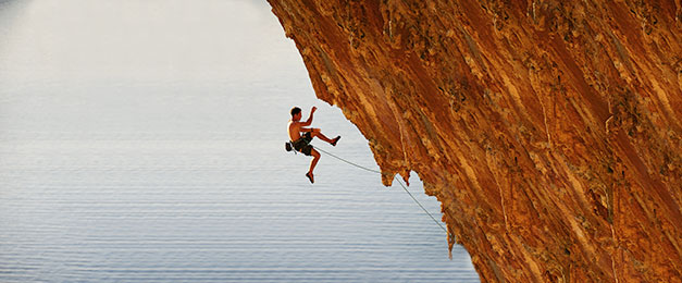Man Abseiling Down a Rock Face
