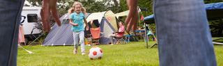 Child plays with football outside of her tent