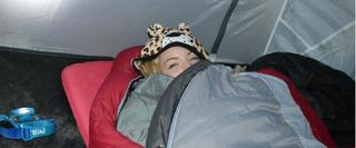 Girl in sleeping bag in tent