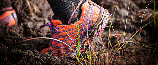 An image of a leg and foot in running sock and Merrell shoe