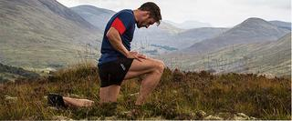 A man on one knee after trail running