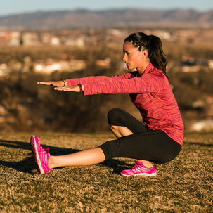 Woman stretches before a run on a hill