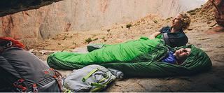Tim Emmett in sleeping bag alongside climbing companion on rocks