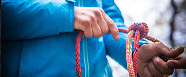 Close up of climber's hands tying climbing rope