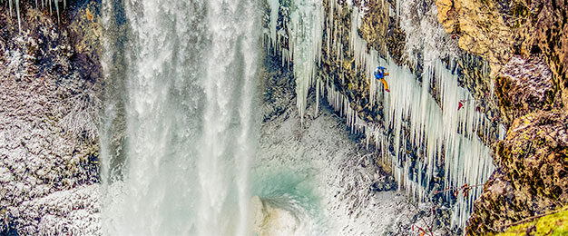 Climber on vertical face with icicles and waterfall