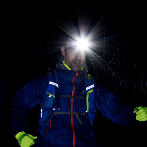 Man running in the dark with a headtorch