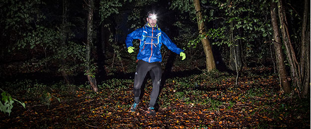 Man Running through forest in the dark wearing running gear and a headtorch