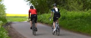 Two women cycling on a road during summer