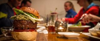 Burger on a table with people eating