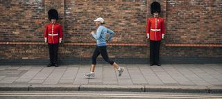 Woman running past guards