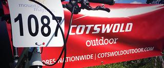 Racing number and bike leaning against Cotswold Outdoor banner
