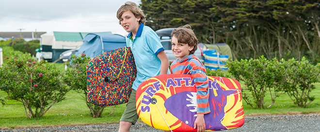 Two boys carrying surf boards